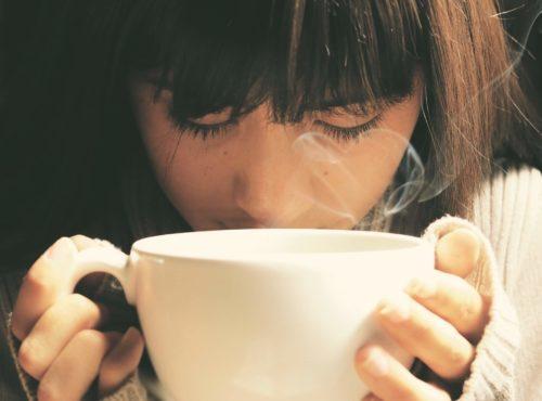 うつむいてコーヒーを飲む女性