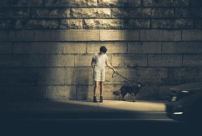 夜犬を散歩させている女性